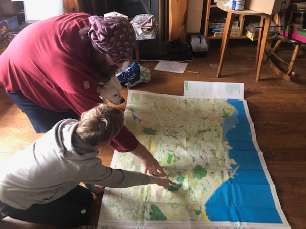 Man, boy and dog looking at a map on a wooden floor